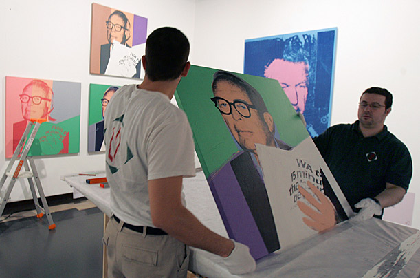 Two museum employees prepare to hang up a painting by US artist Andy Warhol at the Grand Palais in Paris, Friday March 13, 2009.