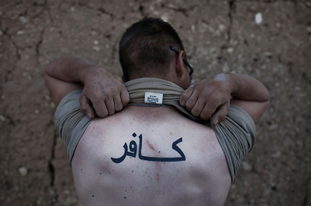 The tattoo on this soldier's back spells kafir, the Arabic word for infidel.