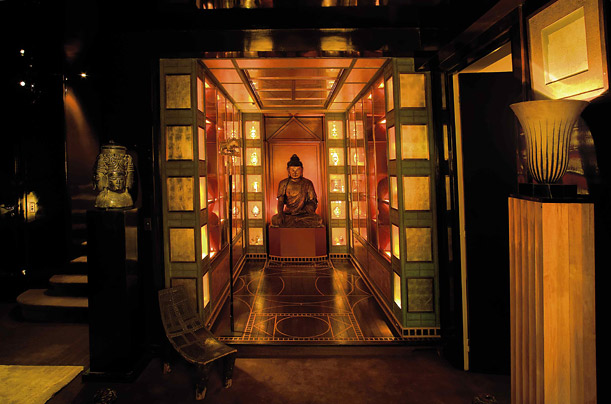 A gold and red lacquered wooden Buddha presides serenely in a room covered by display cases made by the interior designer Jacques Grange
