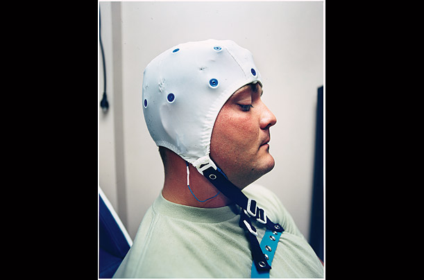 A cap is placed on a soldier as part of a brain-wave analysis that checks for traumatic brain injury.