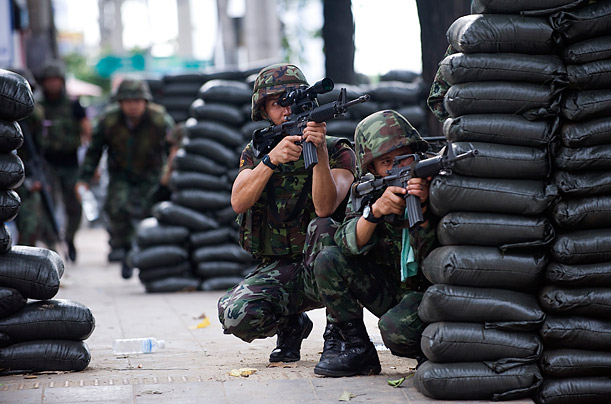 Thai soldiers fire on the protesters from behind sandbags. Over the weekend, the Thai army declared certain protest areas to be a