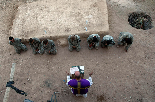Service  Father Subler has used MRE boxes as a makeshift altar for this Mass in the Badula Qulp area. It is not uncommon for the services to be interrupted by the sound of explosions or gunfire.