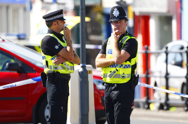 Police officers guard a murder scene in Duke Street in Whitehaven in Cumbria, north west England on Tuesday June 2, 2010.