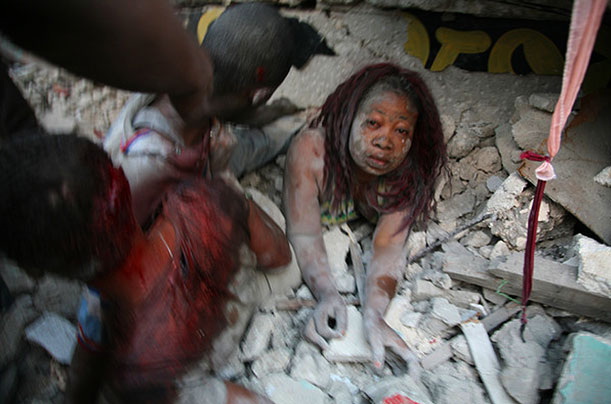 A woman is covered in rubble in Port-au-Prince.