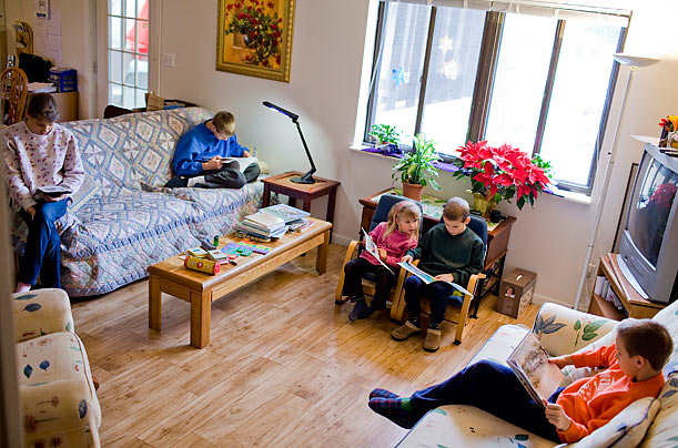 The five children read while their mother prepares lunch.