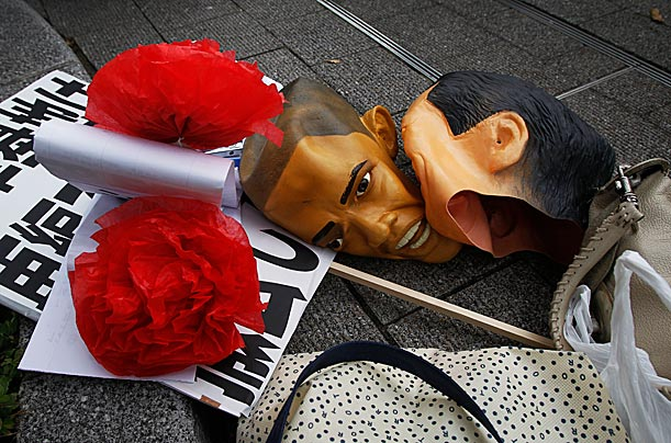 Masks of President Obama and Japanese Prime Minister Naoto Kan, right, lie on the ground during an anti-APEC demonstration near the summit venue.