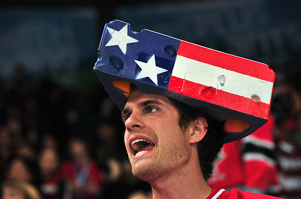 A USA fan with a 'cheese' hat on painted in the national colours cheers during the Women's Ice Hockey preliminary game between USA (blue) against Finland (white)