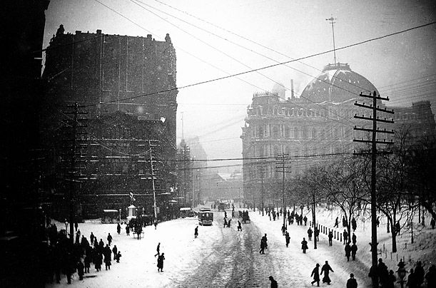 Downtown at 1:30 p.m. on Park Row as people and horse-drawn vehicles struggle to make their way through the snow of the Blizzard of 1888, as seen from the foot path of the Brooklyn Bridge.