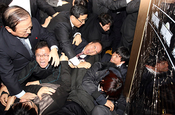 Members of the ruling Grand National Party scuffle with members of opposition parties who blocked entry into the main conference hall of the nation's parliament on December 8,