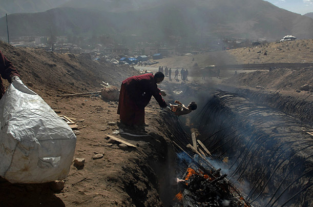 19 April 2010. An ethnic Tibetan monk throws the body of a child onto a funeral pyre in a ditch in Jiegu Town of Yushu County, Qinghai province, after an earthquake hit the area