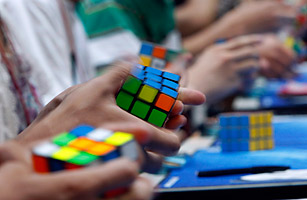 Multiple people competing at Rubik's cube competition