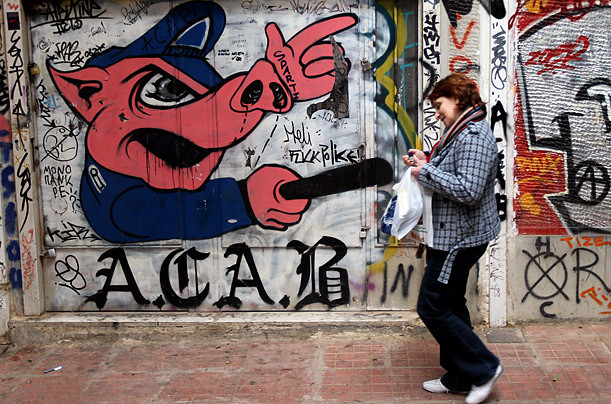 A woman walks by a graffiti-filled wall showing a pig with a truncheon in the center of Athens, Greece, November 14, 2011. The Greek economic crisis and and recession has become a major