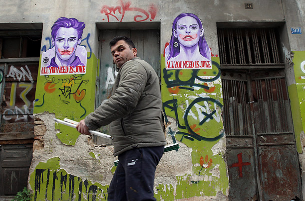 A man walks by graffiti art referencing the Joker from the Batman franchise in the center of Athens, November 15, 2011.