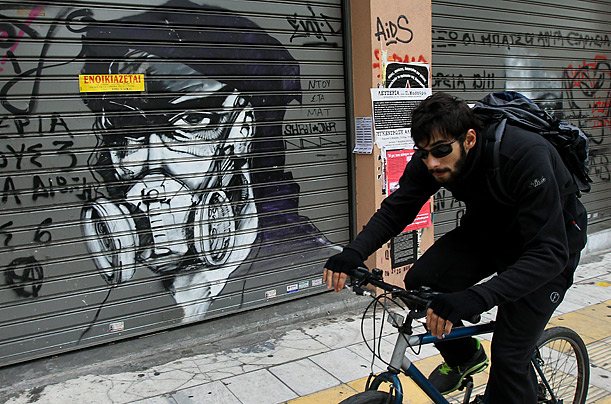 A man rides his bicycle by a graffiti portrait of a protestor in the center of Athens, November 14, 2011.