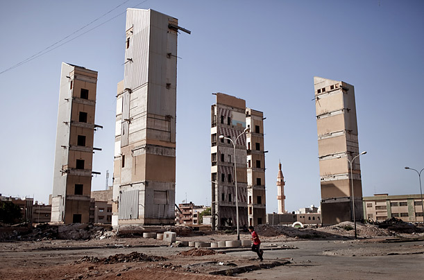 A Libyan boy runs through the ruins of a destroyed building site situated close to a birds market in the Libyan rebel stronghold city of Benghazi, on July 25, 2011.
