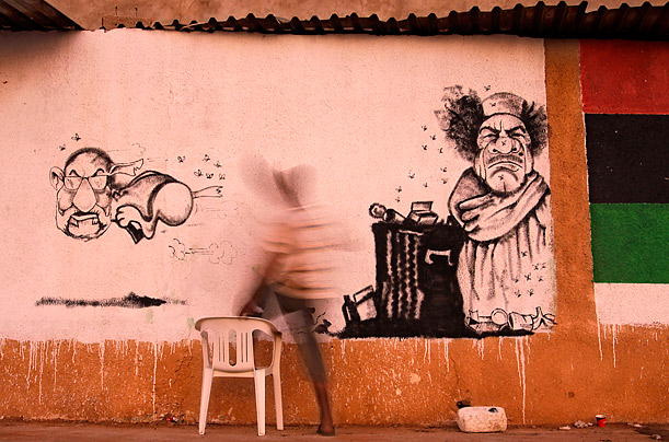 A street artist paints a caricature of Libyan dictator Moammar Gaddafi and his spokesman Abdel-Majid al-Dursi, left, in the rebel-held town of Benghazi, July 21, 2011.