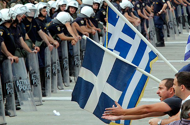 A demonstrator confronts riot police near the Greek parliament in Athens, June 15, 2011.