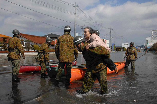 Self-Defense Force officers rescue a woman by a boat in Ishinomaki City.