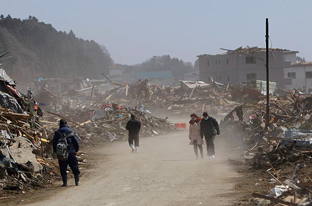 Dust and sand blow through a town leveled by the earthquake.