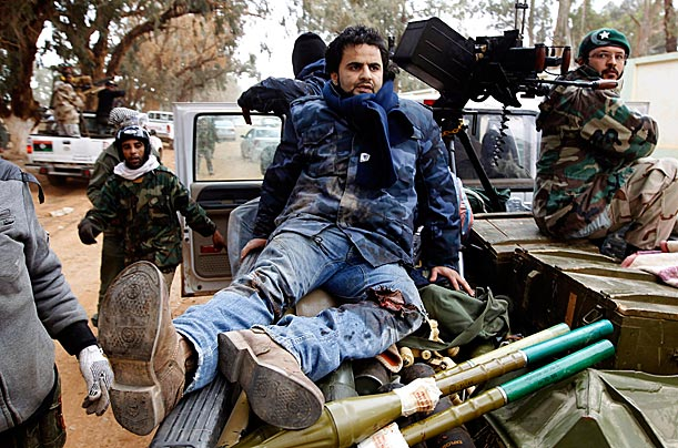 An injured rebel fighter sits in a car as forces loyal to Libyan leader Muammar Gaddafi forces push east despite the declaration of U.N.-mandated no-fly zone over the disputed areas.