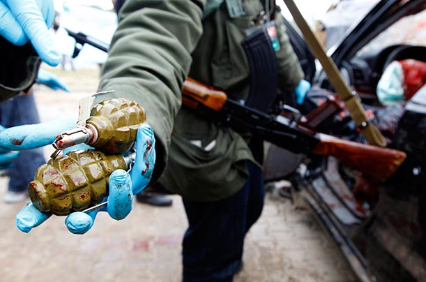 A rebel fighter shows hand grenades found on fighters loyal to  Gaddafi, March 19, 2011.
