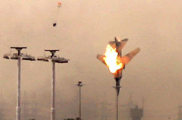 A parachute, upper left, is ejected from a Libyan jet bomber as it crashes after being hit over Benghazi, March 19, 2011.