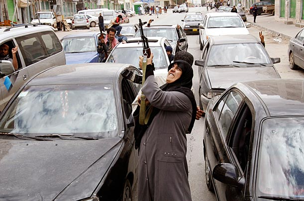 A woman rebel fighter shoots an AK-47 rifle into the air. She had been told that forces loyal to Gaddafi would withdraw from Benghazi (prematurely, it seems), March 19, 2011.