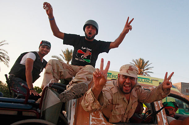 Libyan rebel fighters ride through the town of Mayah celebrating after advancing to the outskirts of Tripoli, August 21, 2011.