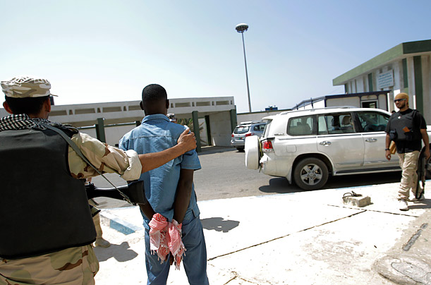 A Libyan rebel holds a captured pro-Gaddafi fighter, center, inside a military base in Tripoli on Monday, August 22, 2011.