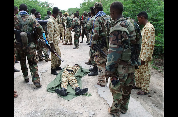 Somali government soldiers gather around the dead body of a fellow government soldier, who was killed during brief exchange of gunfire with Islamist insurgents Al Shabaab in Mogadishu, August, 7, 2011.