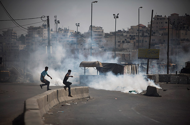 Palestinian protesters use a piece of furniture as a shield during clashes that erupted between Israeli security officers and Palestinian stone-throwers at Qalandiya checkpoint, September 21, 2011.
