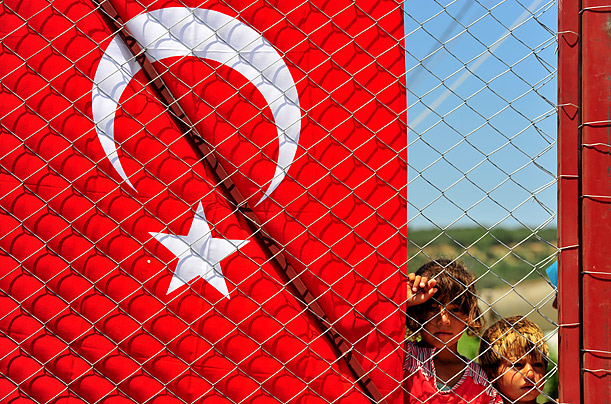 Syrian refugee children stand behind a fence on June 18, 2011 at the Boynuyogun Turkish Red Crescent camp