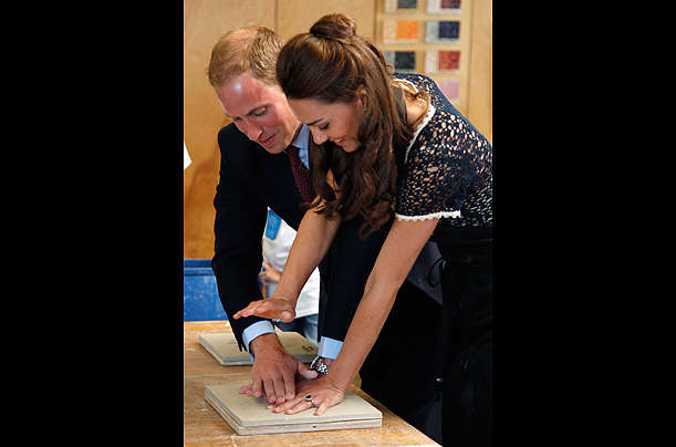 Britain's Prince William and his wife Catherine Duchess of Cambridge press her hands into a piece of clay during the visit to Inner City Arts, July 10, 2011.