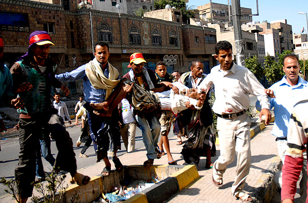 Anti-government protesters carry a wounded man during a shooting on a demonstration held to demand trial of Yemen's outgoing President Ali Abdullah Saleh, in the southern city of Taiz, December 5, 2011.