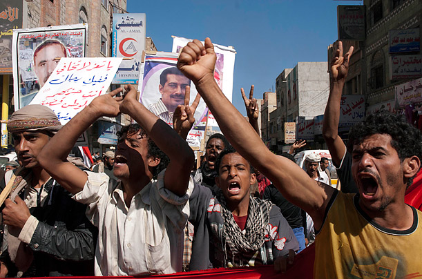 Anti-government protesters shout slogans during a march to demand the ouster of the whole regime of Yemen's outgoing President Ali Abdullah Saleh in the southern city of Taiz,