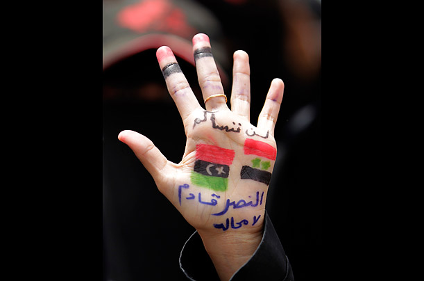A woman at a demonstration in Taiz, June 21, 2011 has fingers painted with the colors of the Yemeni flag and palms showing the flags of Syria and Libya. The slogan reads,