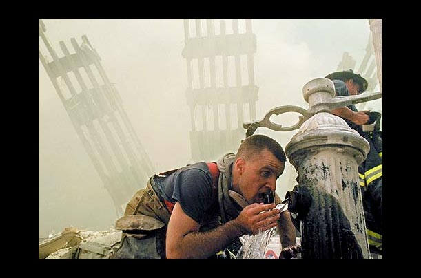 A New York City firefighter drinks water from a fire hydrant