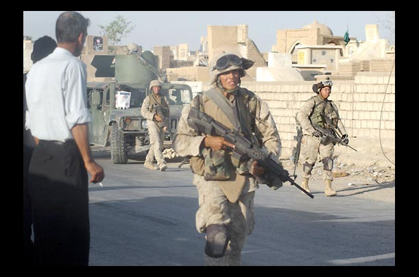 Soldiers of the 11th Marine Expeditionary Unit pass by Iraqi policemen outside Najaf's Wadi al-Salam (Valley of Peace)