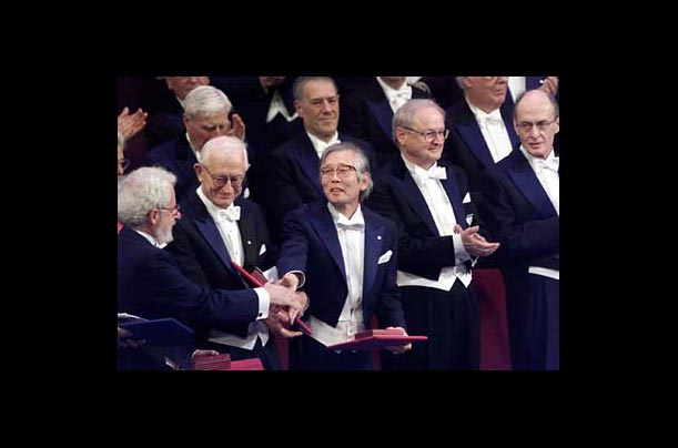 Professor Hideki Shirakawa is congratulated by Nobel laureates after receiving the Nobel Prize in chemistry from the Swedish King, Carl XVI Gustaf, in Stockholm, Sweden