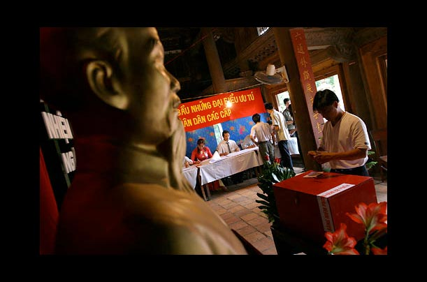 A young man drops his vote in a ballot box at a polling station in Hanoi. Scenes like this played out across Vietnam during April elections for local People's Council representatives