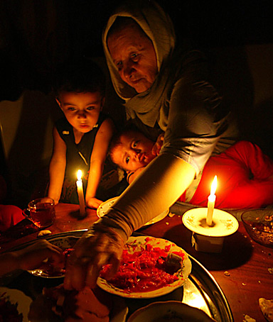 Palestinian family eats dinner by candle light during a power outage