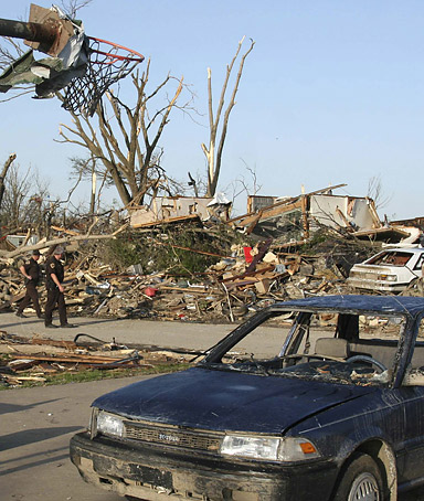 Oklahoma Highway Patrol officers walk down a street of homes destroyed by a tornado in Picher, Oklahoma, May 12, 2008.