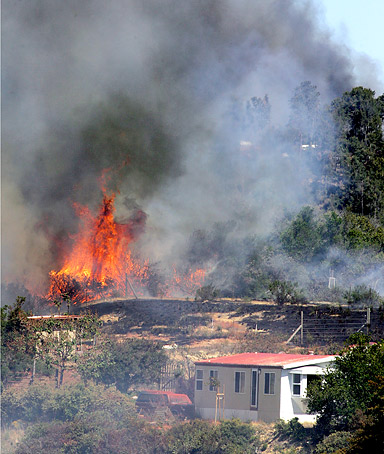 A wildfire looms near a resident's home in Santa Cruz County, California.