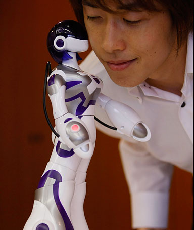 Sega Toy's female humanoid robot, Eternal Maiden Actualisation (E.M.A), kisses a man at its demonstration in Tokyo June 16, 2008