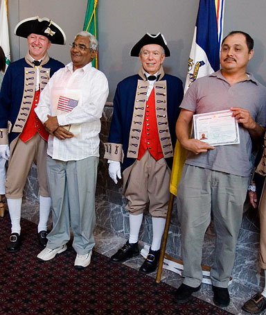 After a naturalization ceremony, new U.S. citizens pose for photographs with members of the Philadelphia Continental Chapter of the Sons of the American Revolution in Philadelphia, Wednesday, July 2, 2008