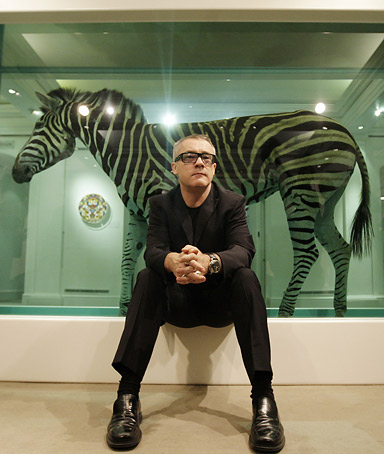British artist Damien Hirst poses for photographs in front of his work entitled 'The Incredible Jouney' during a photocall at Sotheby's art gallery and auction house in central London, on September 8, 2008.