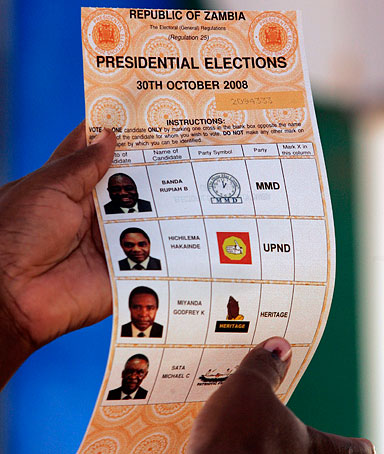 A Zambian Electoral Commission official holds a ballot paper as she explains the voting procedure at Buyuni, 30km east of in Lusaka, Zambia, Thursday Oct. 30, 2008.