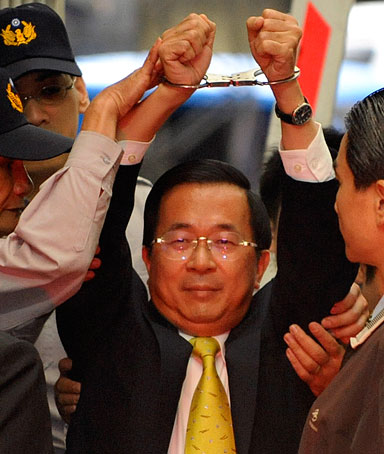 Taiwan's former President Chen Shui-bian shows his handcuffed hands to the media while being sent from the prosecutors' office to the Taipei District Court November 11, 2008.