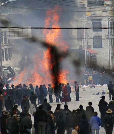 Protesters gather around burning debris in the streets of Lhasa, Tibet, China