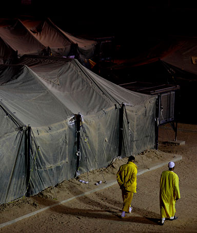 Detainees walk at a U.S. military detention facility Camp Bucca, Iraq, Monday, March 16, 2009.